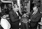 A student receives a Science Explorer T-shirt from Energy Secretary James Watkins and TV news ahchor Bill Kurtis